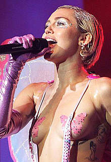 Miley Cyrus almost topless perform on a stage